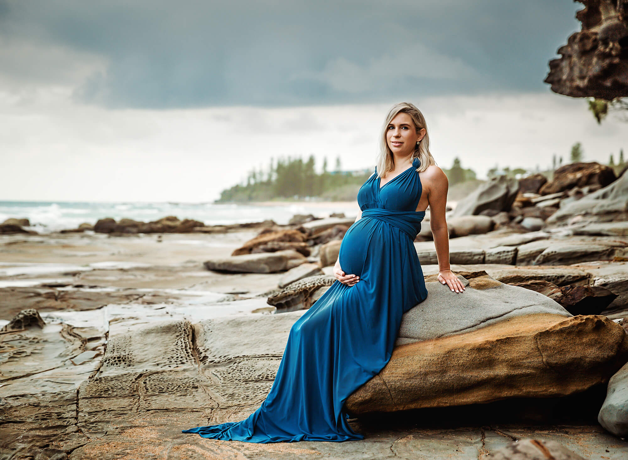 Maternity photo session of a pregnant mother at 36 weeks gestation wearing a stunning dusty blue maternity gown sitting on rocks at shelley beach caloundra