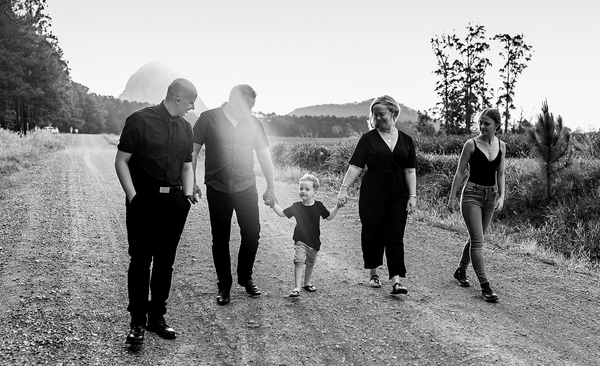 black and white image of a family of 5 walking hand in hand along a dirt road near the glasshouse mountains sunshine coast, qld