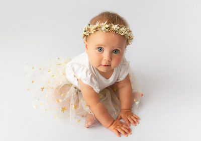 7 month old baby on white backdrop floral crown during sitter session