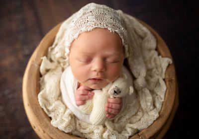 Newborn baby girl in cream in pooh bucket
