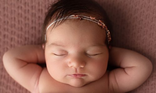 Neborn baby girl relaxing in a posed hands behind head on a dusty pink backdrop in a studio on sunshine coast queensland
