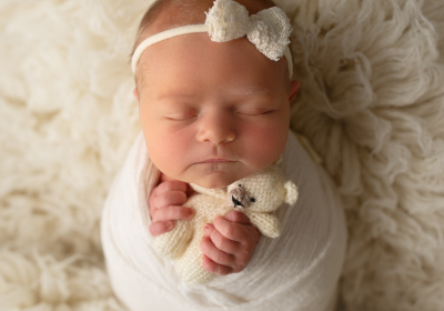 newborn baby girl wrapped in a potato sack pose with cream teddy and cream bow in a newborn photography session on the sunshine coast